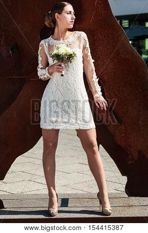 Model pose with stylish wedding gown and bridal bouquet of white roses