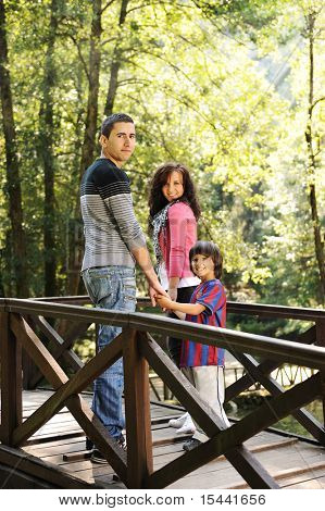 Beautiful scene of young happy family walking in nature together: mother, father and son