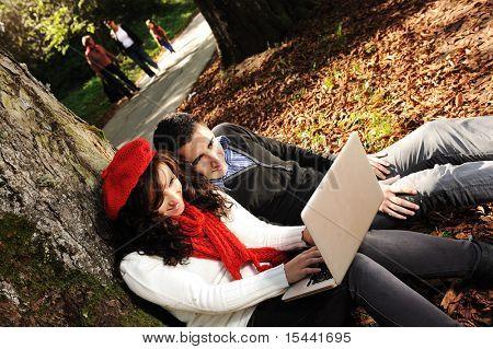 Casal jovem, masculino e feminino sentado no parque, estudando e trabalhando em conjunto com o caderno, caem