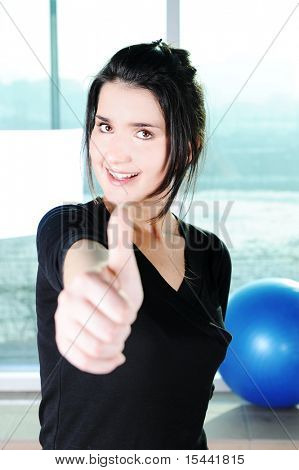 Fitness sporty girl  excercising with a ball at gym and showing a thumb up with smile