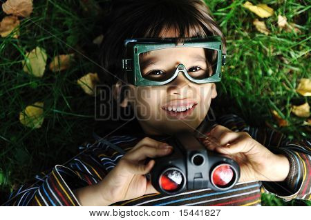 Cute positive boy with glasses and binoculars laying on ground and smiling