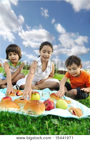 Small group of children eating together in nature, picnic, beautiful scene
