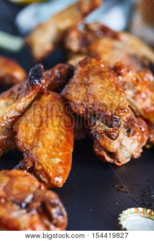 Close-up of spicy chicken buffalo wings. Crispy roasted chicken wings with hot and spicy cayenne pepper sauce on white plate