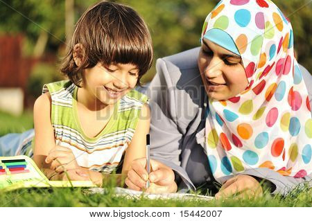 Mother and son learning together in nature, muslim - eastern cultural islamic clothes