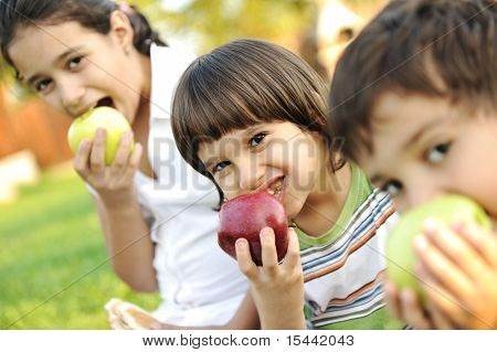 Small group of children eating apples together, shallow DOF