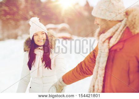 people, season, love and leisure concept - happy couple holding hands and walking along snowy winter field
