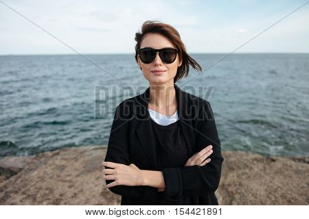 Smiling cute young woman in sunglasses standing with hands folded near the sea