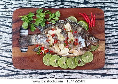 Tilapia fish streamed with lemon topped spicy sour ginger and chili on butcher served. (Call Pla Nil Nuang Manoaw in Thai)