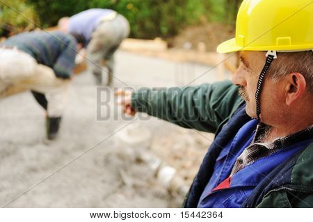 Elderly menager on workplace with workers on fresh concrete