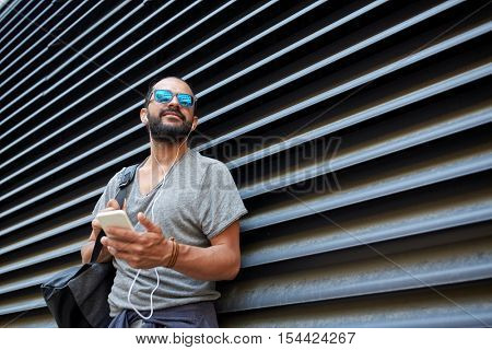 people, technology, travel and tourism - man with earphones, smartphone and bag listening to music on city street