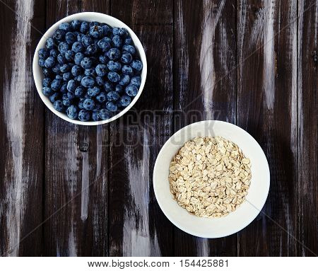 Top view shot of two white bowls with fresh blueberries and raw oat flakes. Perfect, tasty ingredients for delicious and healthy breakfast. Dietary, vitamin and energy booster food on dark wood back