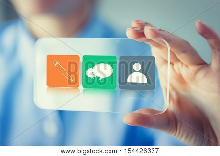 business, technology, communication and people concept - close up of woman hand holding and showing transparent smartphone with messenger icon set on screen
