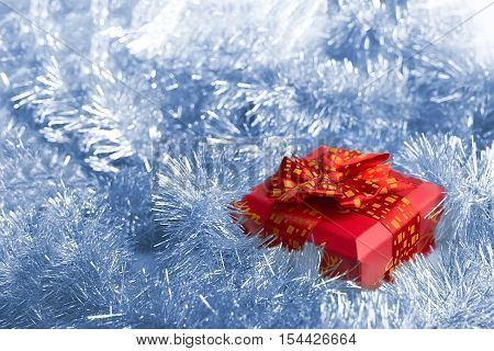 red gift box with a bow on a background of a silvery tinsel