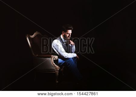 Young handsome bearded caucasian man sitting on vintage sofa. Perfect skin and hairstyle. Wearing vest, white shirt, jeans. Studio portrait with dramatic light