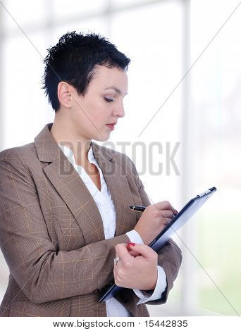 Portrait of a young female entrepreneur taking notes inside a modern building with big glass windows