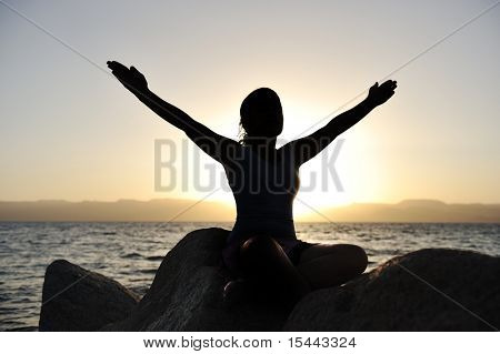 Silhouette of a beautiful female meditating on a rock by the sea