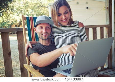 Close-up of a man who is showing something interesting at the screen while a young woman is sitting on his laps. Showing photos that were made during the rest. Spending time together