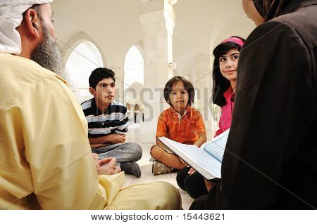 Islamic education inside white mosque, teacher and children learning together (or mother and father with them)