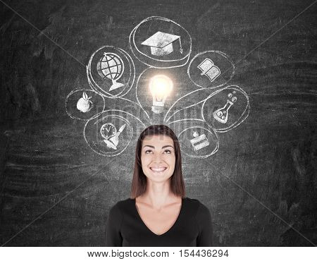 Smiling woman in black is standing near chalkboard with education icons on it. Concept of knowledge gaining