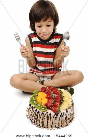 Fantastic fruit cake, colorful and fresh in front of cute boy