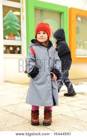 Cute girl outdoor, standing in front of preschool kindergarten