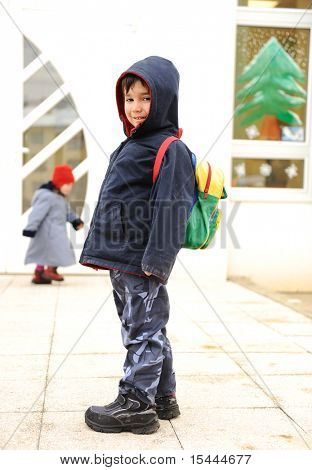 Little cute preschool child with bag on his back