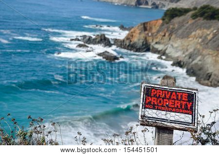 Central California coast with cliffs and blue ocean with private property sign no trespassing