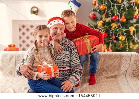 Friendly family is celebrating New Year together. Children are holding gifts and embracing their grandfather. They are sitting on couch and smiling