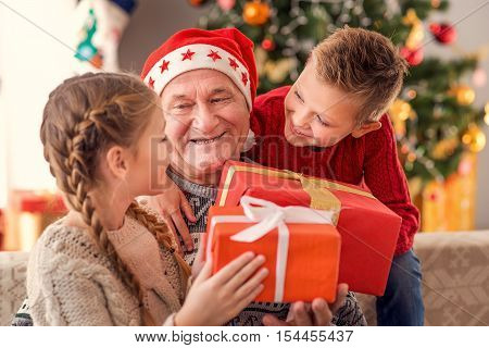 Happy children are receiving Christmas gifts from grandfather. They are sitting at home and smiling