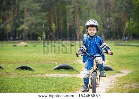 Happy Cute Blond Kid Boy Having Fun His First Bike On Sunny Summer Day