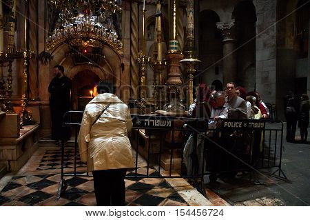 Jerusalem Israel - March 25 2011: Christian pilgrims prays inside the Church of the Holy Sepulchre located in Christian Quarter. The Church considered to be the holiest Christian site in the world