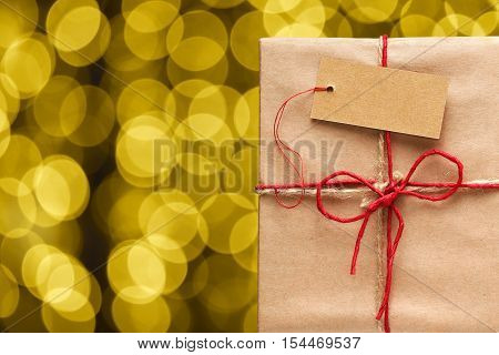 Gift box with tag and golden blurred lights