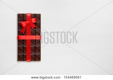 Chocolate bar on white wooden table top view