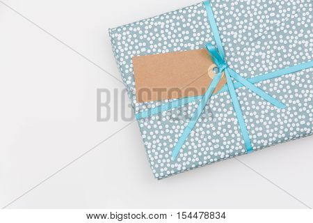 Top view on a wrapped in paper gift for birthday Christmas or other celebration on white wooden background. Gift box with tag and ribbon. Birthday present. Wrapping gift idea.