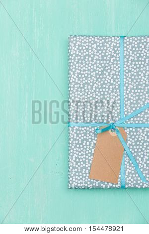 Top view on a wrapped in paper gift for birthday Christmas or other celebration on turquoise wooden background. Gift box with tag and ribbon. Birthday present. Wrapping gift idea.