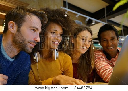 Group of friends websurfing on laptop in coffee shop