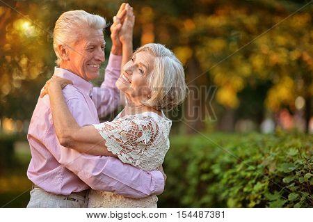 portrait of beautiful caucasian senior couple dancing in the park