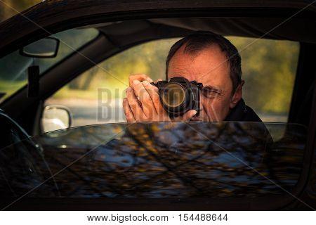 undercover man detective hidden in car secretly take photo