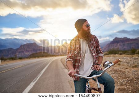 man on side of road riding bike at sunset in Nevada shot with lens flare