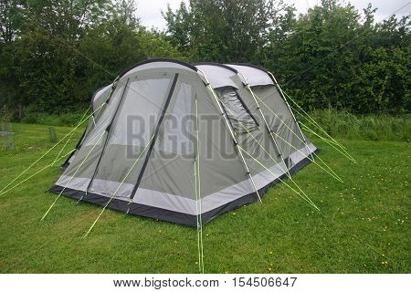 Grey and green four person tent with black sown-in groundsheet. Well guyed with bright yellow guy ropes. Erected on a grass area with trees and sky in the background.