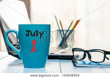 July 1st. Day of the month 1 , color calendar on morning coffee cup at business workplace background. Summer concept. Empty space for text.