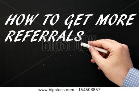 Hand writing the words How To Get More Referrals on a blackboard as a reminder to generate new business and customer sales leads