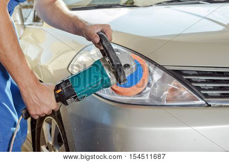 The worker polishes optics of headlights of the car with the electric tool.