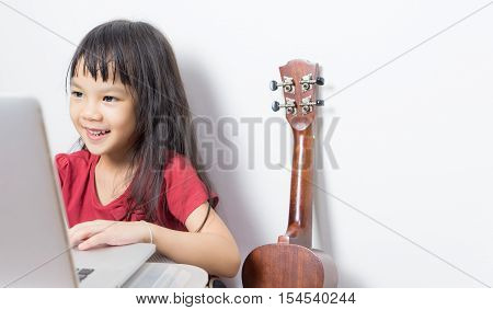 Little musician kid is working on her music on a laptop. Asian kid is looking for music note on the Internet. Japanese girl is taking a guitar music course online.
