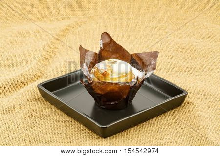 Cruffin creme brulee in black plate place on sackcloth