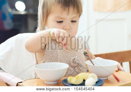 little girl eating with spoon and fork in baby sitting little child eating sour cream with fruits in the home kitchen