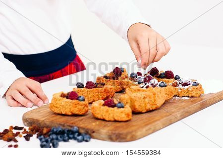 Girl decorating berry cakes with sugar powder, close-up. Young lassie cooking sweet cookies for family. Homemade bakery, children culinary, pastry making concept
