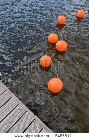 orange buoy group on lake water near wooden bridge