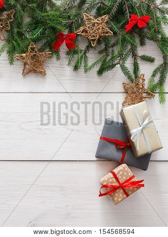 Christmas decoration, gift boxes and garland frame concept background, top view with copy space on white wood table surface. Christmas ornaments and presents border, vertical