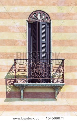 Typical italian balcony with decorative railing and closed window shutters